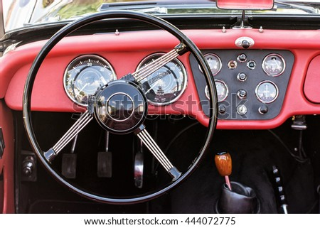 Steering wheel and dashboard in historic vintage red car. Retro automobile interior scene. Driving theme. Old vehicle. - stock photo