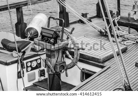 Steering wheel and deck of the old boat - stock photo