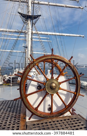 steering wheel and view ahead of a tall ship Gorch Fock - stock photo