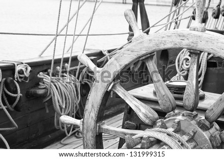 Steering wheel of an ancient sailing vessel. Close up - stock photo