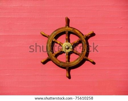 Steering wheel of the ship on a red wall - stock photo