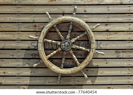 Steering wheel of the ship on a wooden wall of restaurant in marina of Tel-Aviv (Israel) - stock photo