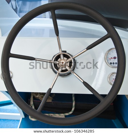 steering wheel on boat - stock photo
