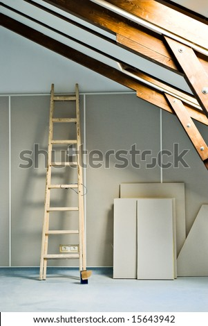 step ladder and construction materials in attic room - stock photo