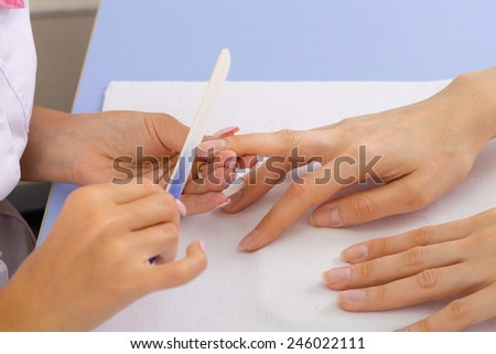 step of manicure process: nails shaping using nail file