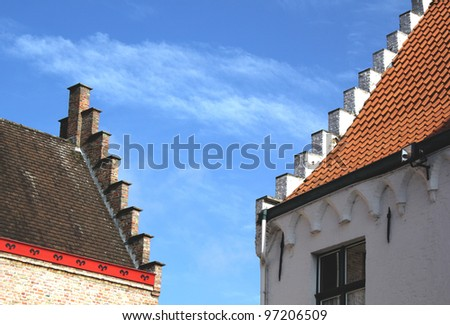 Stepped roof tops of Bruges against a blue sky