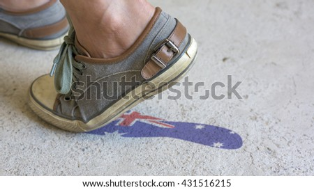 Stepping shoe leaves an Australian flag footprint on the ground.