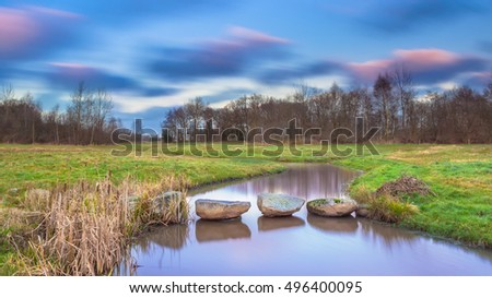 Stepping stones over a Creek with Blurred Clouds by Long Exposure