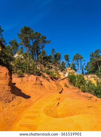 Steps for tourists on a steep slope. Unique red and orange hills in the province of Languedoc - Roussillon, France - stock photo