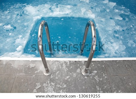 Steps in the frozen blue pool ice-hole - stock photo