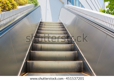 Steps of escalator exit to the street. It symbolizes moving up and forwards. Metal steps and railings.