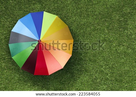 Sterling currency units on colorful umbrella on green grass - stock photo