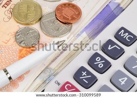 Sterling notes and coins with a pen and calculator. - stock photo