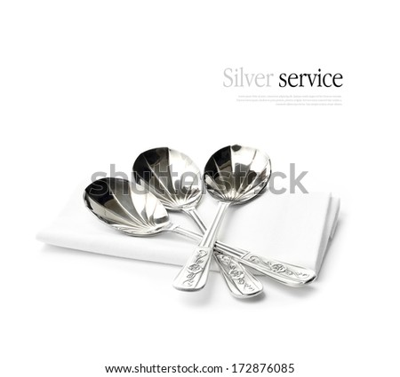 Sterling silver dessert spoons with subtle reflections on a folded napkin against a white background. Perfect image for a dining or restaurant design. Copy space.
