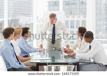 Stern businessman looking down at his staff during a meeting in the office
