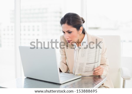 Stern businesswoman holding newspaper while working on laptop at the office