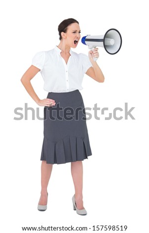Stern businesswoman shouting in her megaphone while posing on white background