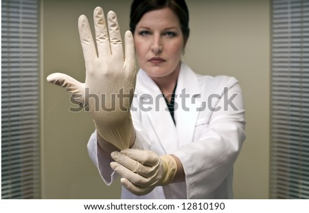 Stern Doctor Pulling on a Rubber Glove - stock photo