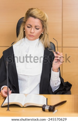 Stern judge reading her notes in the court room - stock photo