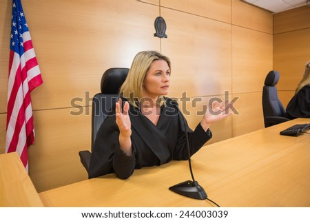 Stern judge speaking to the court in the court room - stock photo