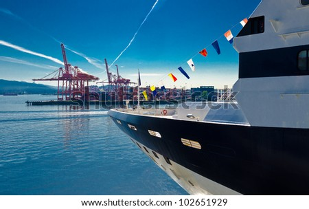 Stern of a cruise ship moving into the inlet  ( out of the harbor ) with the container port terminal on starboard ( right ) side. - stock photo