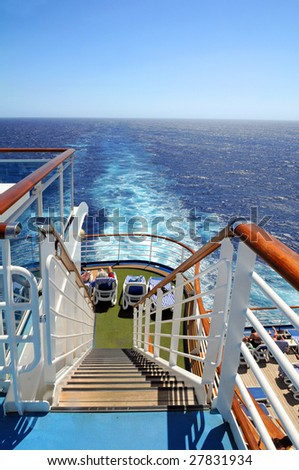Stern of cruise ship with water wake from engines - stock photo