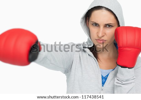 Stern woman in sweatshirt boxing against white background