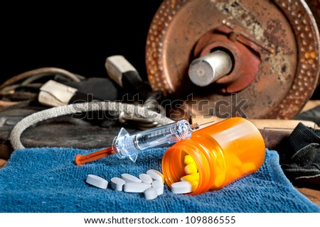 Steroid medication including pills and a syringe in front of exercise equipment.  Image can be used for steroid and performance enhancement inferences in sports. - stock photo