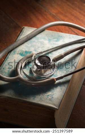 Stethocope on antique book. - stock photo