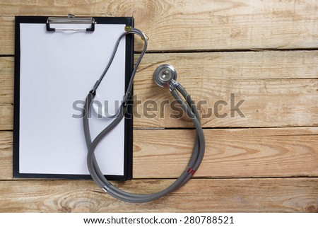 Stethoscope and clipboard on wood table top view . Medical background. Concept for diet, healthcare, nutrition or medical insurance - stock photo