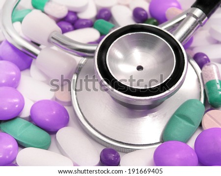 stethoscope and colored pills  - stock photo