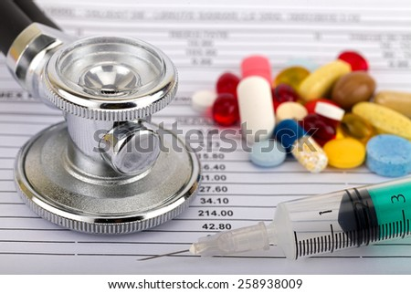 Stethoscope and colourful pills over medical record
