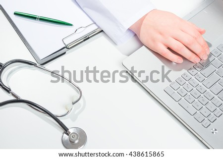 stethoscope and doctor's hand close-up view from above - stock photo