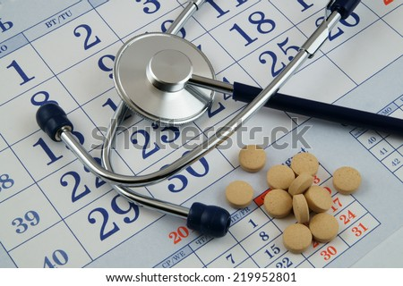 Stethoscope and drugs on calendar, medical concept