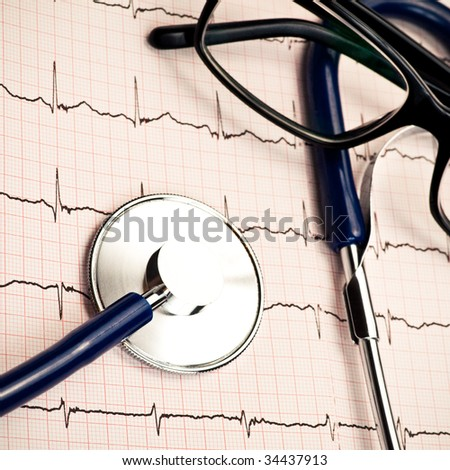 Stethoscope and glasses lying on ECG diagram