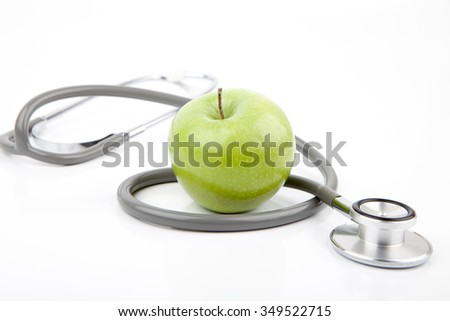 Stethoscope and green apple on white - stock photo