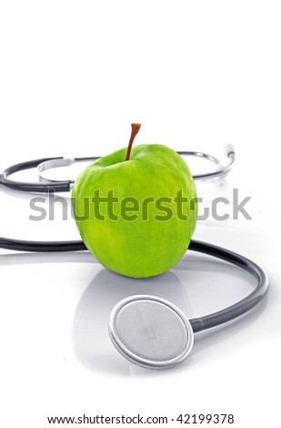 Stethoscope and green apple on white background