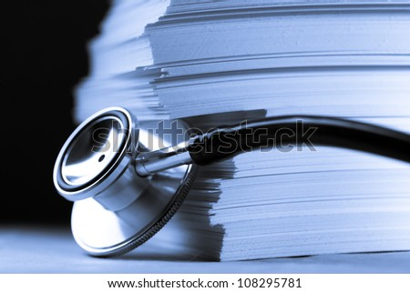 Stethoscope and heap of paper cards - stock photo