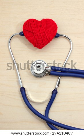 stethoscope and heart symbol of red thread on a wooden table - stock photo