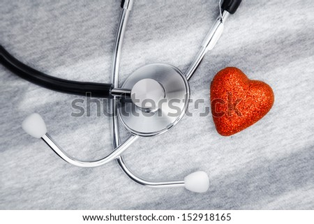 Stethoscope and heart symbol on a table with shadows - stock photo