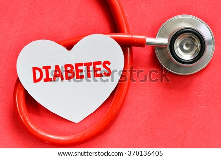 Stethoscope and heart symbol with inscription diabetes on red background - stock photo