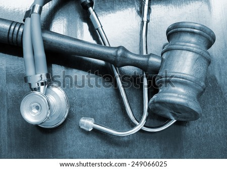Stethoscope and judge gavel and on wooden table - stock photo