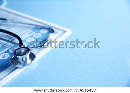 Stethoscope and medical equipment on a light blue background - stock photo