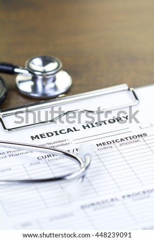Stethoscope and Medical History Report Isolated on Brown Wooden Desktop with Upper Space