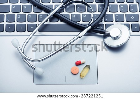Stethoscope and medicine on laptop computer - stock photo