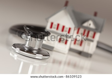 Stethoscope and Model House on Gradated Background with Selective Focus. - stock photo