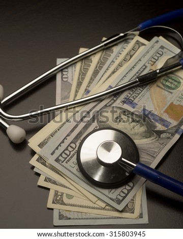 Stethoscope and money/Money and Medicine/Medical cost illustrated with a stethoscope and large denominations