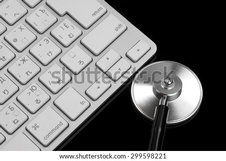 Stethoscope And Multilingual  Wireless Keyboard Isolated On Black Glass Background With Reflection. Technical Support Or Repair Service  Or Information Security Concept - stock photo