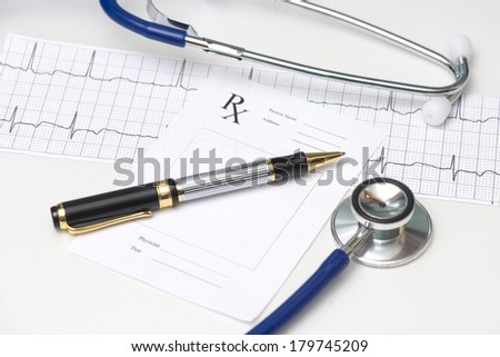 Stethoscope and pen with prescription and electrocardiograph.