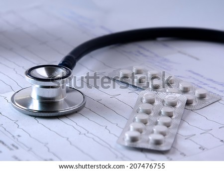 Stethoscope and pills on the cardiogram - stock photo